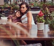 Portrait de maman à la mode et de sa belle fille pendant un moment dans un café extérieur Images stock
