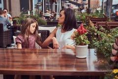 Portrait de maman à la mode et de sa belle fille pendant un moment dans un café extérieur Image stock