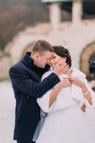 Portrait de mariage d'hiver Nouveaux mariés heureux embrassant dans neigé vers le haut du parc, partageant la chaleur de leurs se Photographie stock