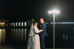 Portrait de mariage romantique Jeunes mariés se tenant près du lac de nuit illuminé avec des lumières de hall de banquet Photos stock