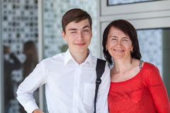 Portrait de mather heureux avec le fils sur le mur blanc, Photo stock