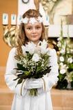 Portrait de mignon petite fille sur la robe et la guirlande blanches sur la première porte d'église de fond de sainte communion photos libres de droits