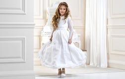 Portrait de mignon petite fille sur la robe et la guirlande blanches sur la première porte d'église de fond de sainte communion images stock