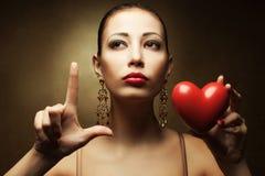 Portrait de modèle à la mode avec les lèvres rouges sexy tenant le coeur rouge Photographie stock libre de droits