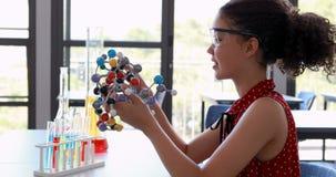 Portrait de modèle de expérimentation de molécule d'écolière heureuse dans le laboratoire banque de vidéos
