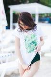 Portrait de mode d'été de femme renversante avec le corps sexy convenable bronzé, T-shirt blanc de port avec la copie verte, mail photo stock