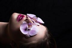 Portrait de mode de fille avec l'orchidée de fleur Sur un backgrou noir Photos libres de droits
