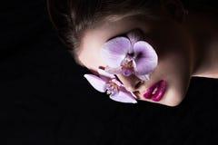 Portrait de mode de fille avec l'orchidée de fleur Sur un backgrou noir Photo libre de droits