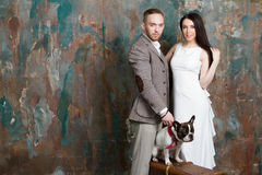 Portrait de mode de jeunes mariés de couples de mariage avec le chien et la valise Image libre de droits