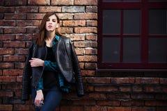 Portrait de mode de mode de vie de fille de brune dans le style de noir de roche, se tenant dehors dans la rue de ville Photos stock
