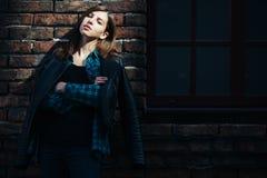 Portrait de mode de mode de vie de fille de brune dans le style de noir de roche, se tenant dehors dans la rue de ville Image libre de droits