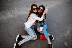 Portrait de mode de vie d'été de deux femmes élégantes de hippie avec le corps sexy d'ajustement, l'équipement de port de denim e Photo stock