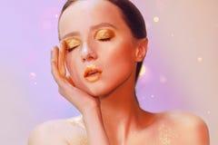 Portrait de mode de jeune fille élégante Fond coloré, tir de studio Belle femme de brune avec des lèvres d'or et lumineux d'or Photos libres de droits