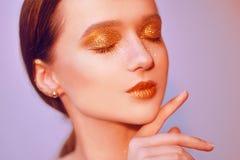Portrait de mode de jeune fille élégante Fond coloré, tir de studio Belle femme de brune avec des lèvres d'or et lumineux d'or Images stock