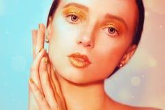 Portrait de mode de jeune fille élégante Fond coloré, tir de studio Belle femme de brune avec des lèvres d'or et lumineux d'or Photographie stock libre de droits
