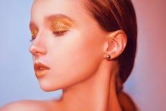 Portrait de mode de jeune fille élégante Fond coloré, tir de studio Belle femme de brune avec des lèvres d'or et lumineux d'or Images libres de droits