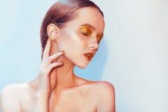 Portrait de mode de jeune fille élégante Fond de Paslet, tir de studio Belle femme de brune avec des lèvres d'or et lumineux d'or Images stock