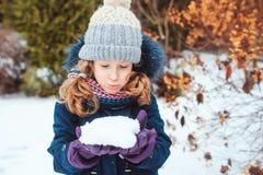 portrait de mode de vie d'hiver de la fille heureuse d'enfant jouant des boules de neige sur la promenade Image stock