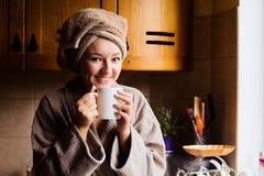 Portrait de mode de vie d'un beau café potable de matin de jeune fille dans sa cuisine Photos stock