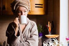 Portrait de mode de vie d'un beau café potable de matin de jeune fille dans sa cuisine Images libres de droits
