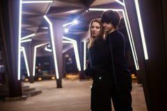 Portrait de mode de vie des couples dans l'amour sur les rues de ville avec beaucoup de lumières sur le fond Photos stock