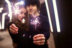 Portrait de mode de vie des couples dans l'amour tenant les feux d'artifice de scintillement de nouvelle année sur les rues de vi Photo stock