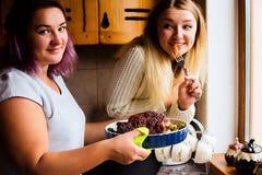 Portrait de mode de vie de deux jeunes femmes heureuses avec la dinde cuite au four pour le dîner de thanksgiving Image libre de droits