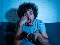 Portrait de mode de vie du sentiment étant ennuyeux de observation du jeune homme millénaire TV somnolent la nuit photo stock