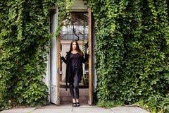 Portrait de mode de vie de fille portant le T-shirt, les jeans vides et le manteau noirs posant contre le bâtiment couvert de feu images stock
