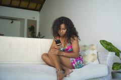 Portrait de mode de vie de jeune salon américain de femme d'africain noir heureux et magnifique à la maison utilisant le networ d image stock
