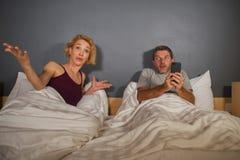 Portrait de mode de vie de mari ou d'ami à l'aide du téléphone portable dans le lit avec sentiment frustrant fâché d'épouse ou d' images libres de droits