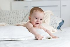 Portrait de 9 mois adorables de bébé garçon se trouvant sur le grand oreiller sur le lit Photographie stock