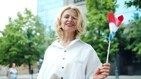 Portrait de mouvement lent de dame mûre se tenant dehors tenant le drapeau français clips vidéos