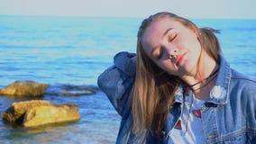 Portrait de mouvement lent de femme douce avec le léger sourire sur des lèvres contre la mer et le ciel bleus la soirée tranquill banque de vidéos