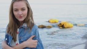 Portrait de mouvement lent de fille mignonne posant et souriant à l'appareil-photo, mer se tenante prêt la soirée chaude d'été banque de vidéos