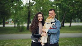 Portrait de mouvement lent des propriétaires fiers de chien de l'homme et de femme tenant le chiot adorable, regardant l'appareil banque de vidéos