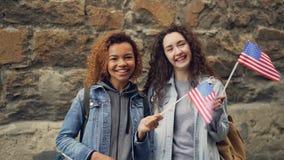 Portrait de mouvement lent de deux jeunes femmes d'amis dans des vêtements sport ondulant les drapeaux américains et riant regard banque de vidéos