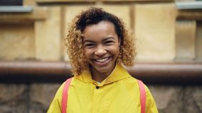 Portrait de mouvement lent de femme heureuse d'Afro-américain avec les cheveux bouclés regardant l'appareil-photo et souriant alo banque de vidéos
