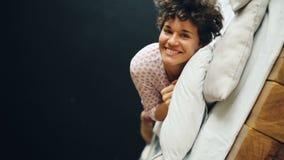 Portrait de mouvement lent de femme insouciante dans le roulement de vêtements décontractés dans le double lit ayant l'amusement  clips vidéos