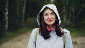 Portrait de mouvement lent de jeune femme attirante souriant et regardant l'appareil-photo se tenant dans la forêt avec de hauts  banque de vidéos