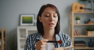 Portrait de mouvement lent de jolie dame appliquant la poudre de visage avec le sourire de brosse banque de vidéos