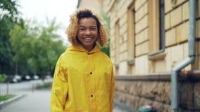 Portrait de mouvement lent de la femme de sourire d'Afro-américain dans le manteau lumineux marchant dans la rue, se tournant ver banque de vidéos