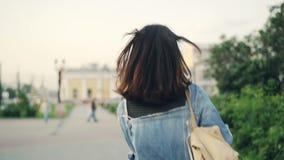 Portrait de mouvement lent de touriste aux cheveux foncés heureuse de fille avec le sac à dos courant et tournant regarder l'appa clips vidéos