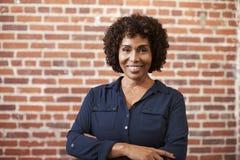 Portrait de mur mûr de sourire de Standing Against Brick de femme d'affaires dans le bureau moderne image stock