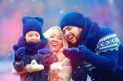 Portrait de neige de soufflement d'hiver de famille heureuse dehors, saison des vacances photographie stock