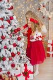 Portrait de Noël de deux amies de sourire de soeurs de filles mignonnes beautyful et d'arbre blanc vert de luxe de Noël dans le s Photos libres de droits