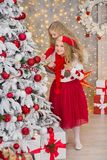 Portrait de Noël de deux amies de sourire de soeurs de filles mignonnes beautyful et d'arbre blanc vert de luxe de Noël dans le s Images libres de droits