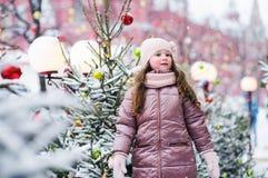Portrait de Noël de jouer heureux de fille d'enfant extérieur dans le jour d'hiver neigeux, sapins décorés pendant des vacances d photographie stock