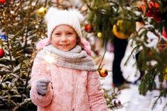 portrait de Noël de la fille heureuse d'enfant tenant le cierge magique brûlant ou du feu d'artifice extérieur photographie stock