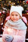 portrait de Noël de la fille heureuse d'enfant tenant le cierge magique brûlant ou du feu d'artifice extérieur photos libres de droits